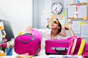 stock -- businesswoman, vacation, trip, weekend, travel, work, office, Smiling female office worker ready to leave for vacations with pink luggage.; Shutterstock ID 225404176